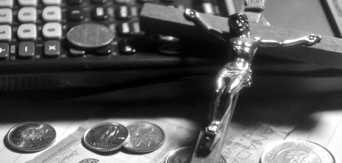 Stylized photo of a laptop, money, and a crucifix