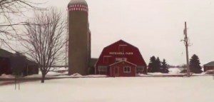 Photo of a red barn and silo in the snow