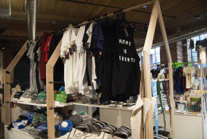 """T-shirts of different colours hang in the Spacing Store Toronto. The first one says """"Home is Toronto"""" on the front."""