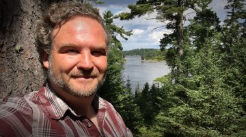John Thompson poses in front of a Nothern Ontario forest and lake. Photo courtesy John Thompson.