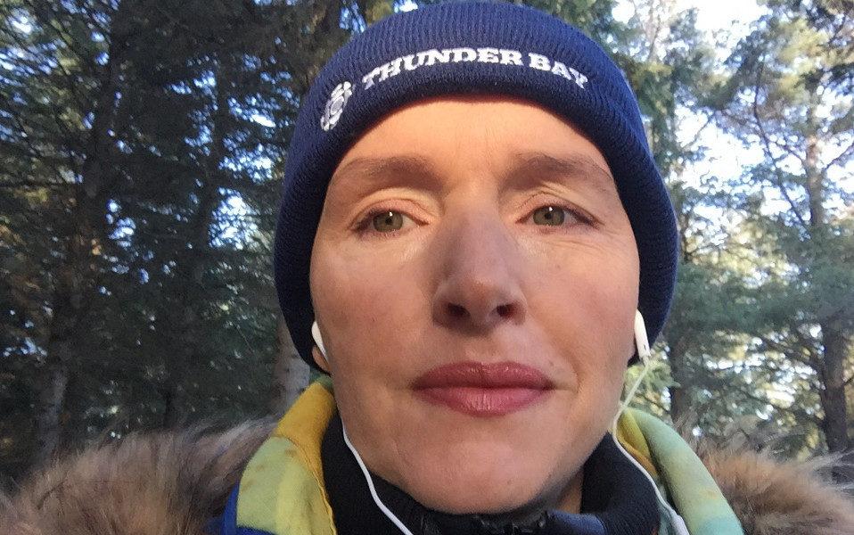 Journalist Jody Porter taking a photo of herself in a forest