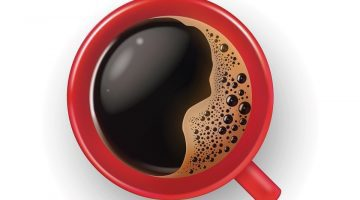 A cup of black coffee with foam at the top