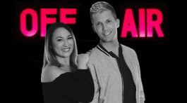 """Radio hosts Jesse and Jenna stand in front of a neon """"Off Air"""" sign"""
