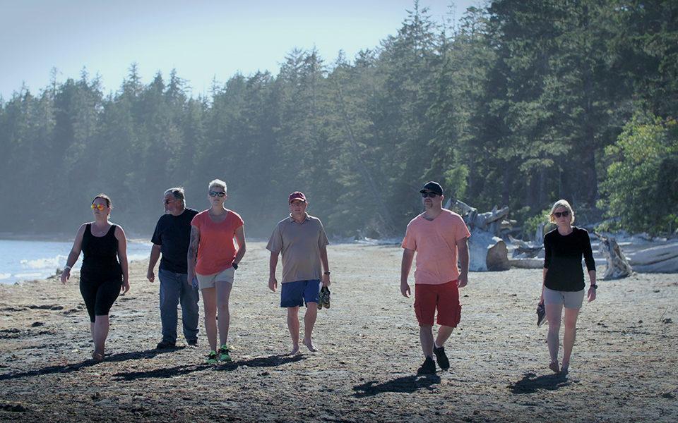 A group of people walk along a beach