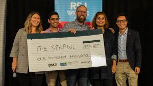 Natasha Campagna (DMZ Sandbox), Ashutosh Syal (DMZ Sandbox), Jeremy Klaszus (The Sprawl), Asmaa Malik (Ryerson School of Journalism), Kevin Chan (Facebook), stand on stage holding a cheque