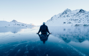 A person sits on an ice-covered lake with their back to the camera