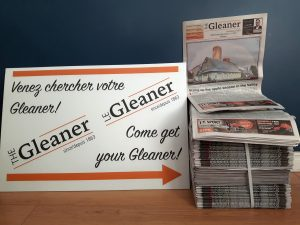 """A white sign reading """"Come get your Gleaner"""" in English and French points to a stack of newspapers."""