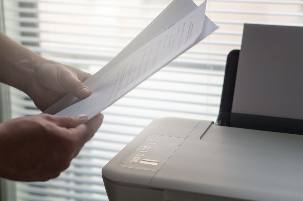 A person holds sheets of paper beside a printer.